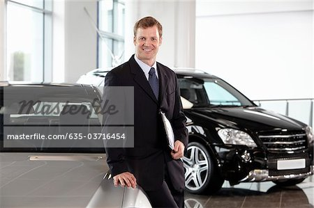 Salesman leaning on new car in showroom Stock Photo - Premium Royalty-Free, Image code: 635-03716454