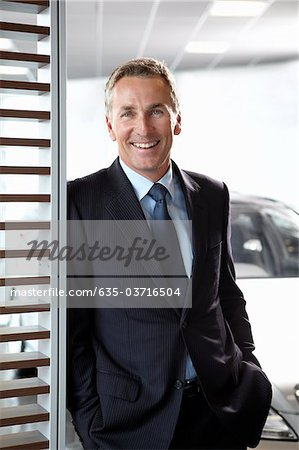 Salesman standing in automobile showroom Stock Photo - Premium Royalty-Free, Image code: 635-03716504