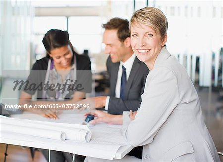 Business people looking at blueprints together Stock Photo - Premium Royalty-Free, Image code: 635-03752298
