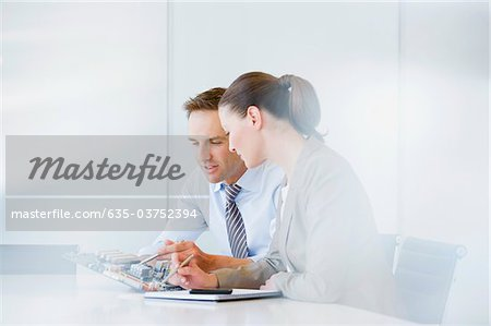 Business people looking at circuit board in office Stock Photo - Premium Royalty-Free, Image code: 635-03752394