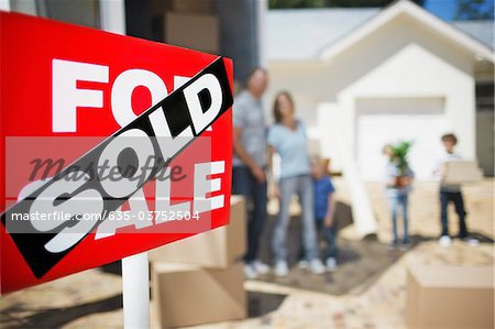 Sold sign on house with family in the background Stock Photo - Premium Royalty-Free, Image code: 635-03752504