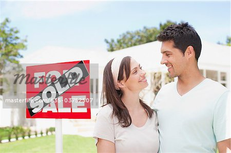Couple standing near sold sign of their new house Stock Photo - Premium Royalty-Free, Image code: 635-03752507