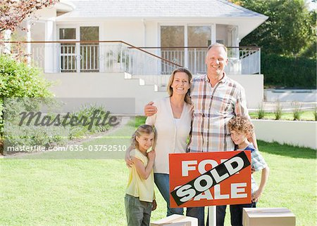 Family standing with sold sign of their new house Stock Photo - Premium Royalty-Free, Image code: 635-03752510