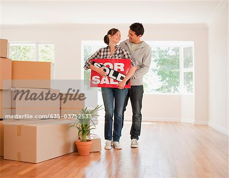 Couple holding sold sign for their new house Stock Photo - Premium Royalty-Free, Image code: 635-03752533