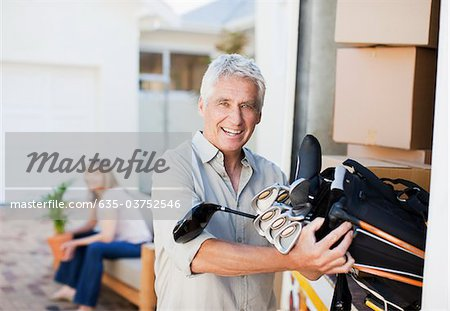 Man removing golf clubs from moving van Stock Photo - Premium Royalty-Free, Image code: 635-03752546