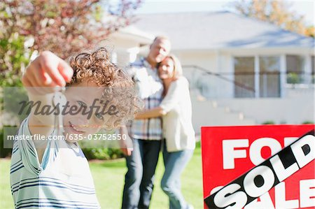 Boy holding new house keys next to sold sign Stock Photo - Premium Royalty-Free, Image code: 635-03752550