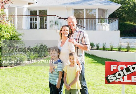 Family standing in front yard of new house next to sold sign Stock Photo - Premium Royalty-Free, Image code: 635-03752591