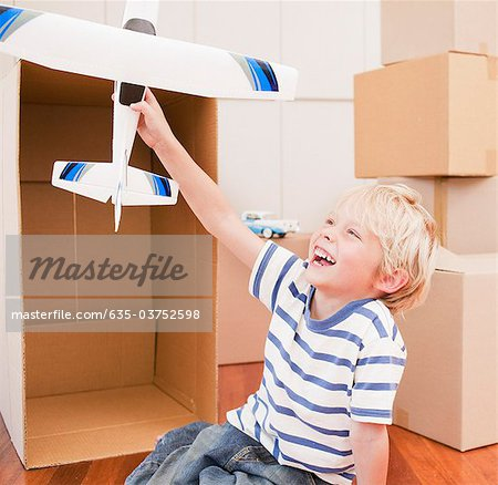 Grinning boy playing with model airplane in his new house Stock Photo - Premium Royalty-Free, Image code: 635-03752598
