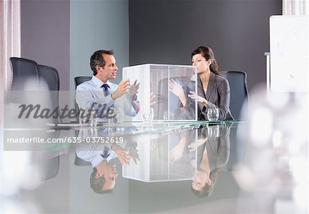 Business people looking at transparent cube in conference room Stock Photo - Premium Royalty-Free, Image code: 635-03752619