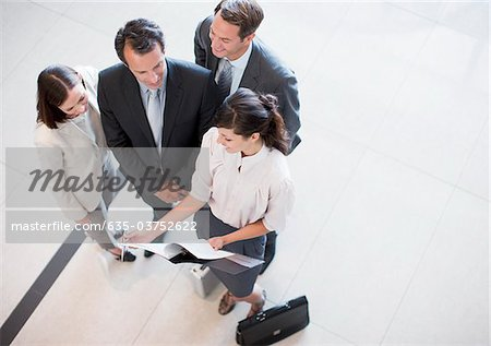 Business people reviewing report in office lobby Stock Photo - Premium Royalty-Free, Image code: 635-03752622