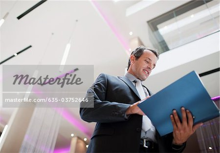 Businessman reading report in lobby Stock Photo - Premium Royalty-Free, Image code: 635-03752646