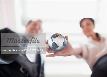 Businesswoman holding small globe in office Stock Photo - Premium Royalty-Free, Image code: 635-03752688