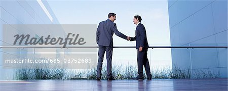Businessmen shaking hands on balcony Stock Photo - Premium Royalty-Free, Image code: 635-03752689