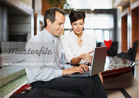 Business people working together in hotel lobby Stock Photo - Premium Royalty-Free, Image code: 635-03752702