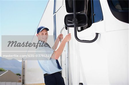Truck driver standing on side of semi-truck Stock Photo - Premium Royalty-Free, Image code: 635-03781323