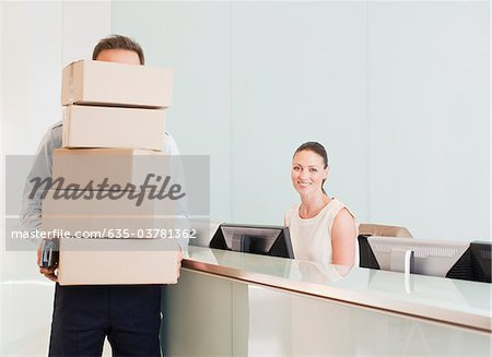 Delivery man holding stack of boxes in reception area Stock Photo - Premium Royalty-Free, Image code: 635-03781362