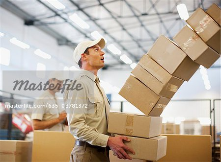 Worker dropping boxes in shipping area Stock Photo - Premium Royalty-Free, Image code: 635-03781372
