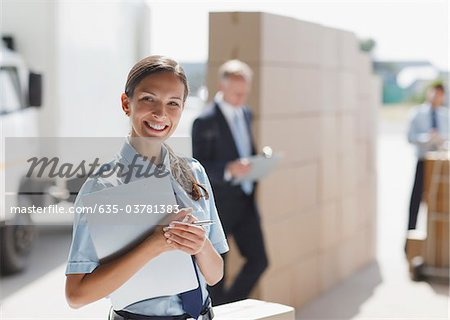 Worker standing with clipboard in shipping area Stock Photo - Premium Royalty-Free, Image code: 635-03781383