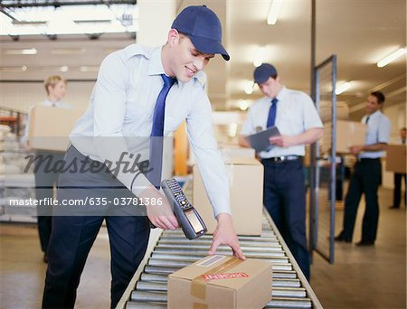 Worker scanning box on conveyor belt in shipping area Stock Photo - Premium Royalty-Free, Image code: 635-03781386