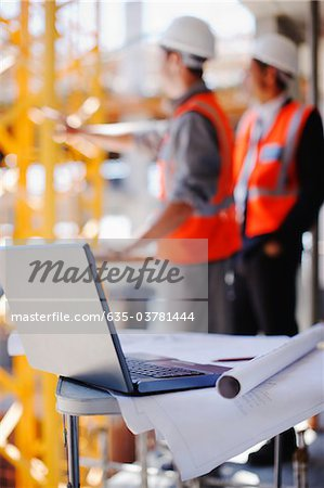 Construction workers behind laptop and blueprints on construction site Stock Photo - Premium Royalty-Free, Image code: 635-03781444