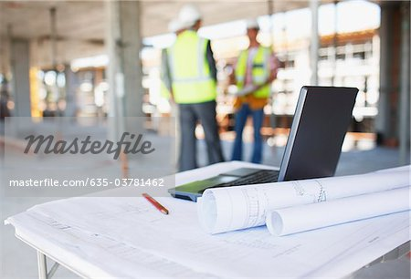 Construction workers behind blueprints and laptop on construction site Stock Photo - Premium Royalty-Free, Image code: 635-03781462