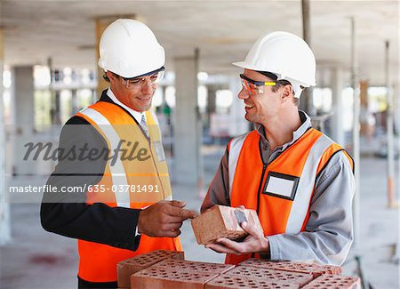 Construction workers looking at bricks on construction site Stock Photo - Premium Royalty-Free, Image code: 635-03781491