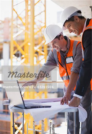 Construction workers using laptop on construction site Stock Photo - Premium Royalty-Free, Image code: 635-03781506