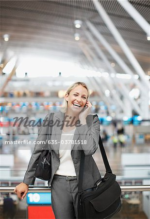 Businesswoman talking on cell phone in office Stock Photo - Premium Royalty-Free, Image code: 635-03781518