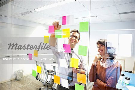 Business people looking at adhesive notes in conference room Stock Photo - Premium Royalty-Free, Image code: 635-03781525