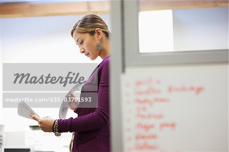 Businesswoman looking at paperwork in office Stock Photo - Premium Royalty-Free, Image code: 635-03781593