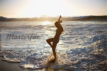 Woman standing in ocean waves Stock Photo - Premium Royalty-Free, Image code: 635-03781665