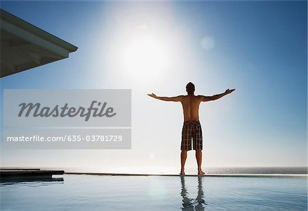 Man standing near swimming pool with arms outstretched Stock Photo - Premium Royalty-Free, Image code: 635-03781729