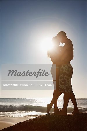 Couple hugging on rock near ocean Stock Photo - Premium Royalty-Free, Image code: 635-03781746
