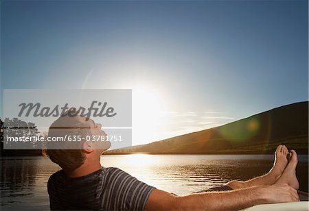 Man relaxing near lake at sunset Stock Photo - Premium Royalty-Free, Image code: 635-03781751