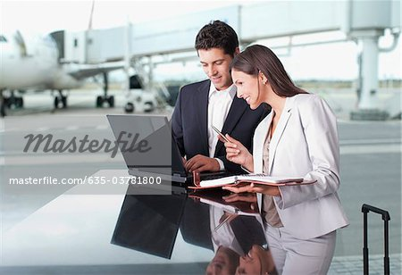 Business people using laptop together at airport Stock Photo - Premium Royalty-Free, Image code: 635-03781800