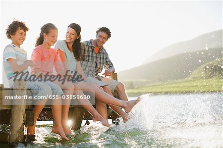 Family on dock splashing feet in lake Stock Photo - Premium Royalty-Free, Image code: 635-03859690