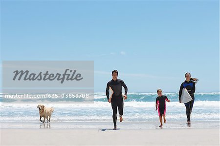 Family with surfboards running on beach Stock Photo - Premium Royalty-Free, Image code: 635-03859708