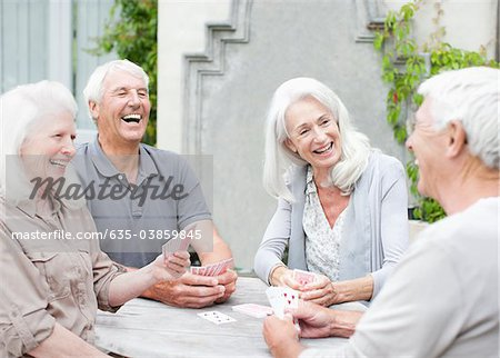 Senior couples playing cards on patio Stock Photo - Premium Royalty-Free, Image code: 635-03859845