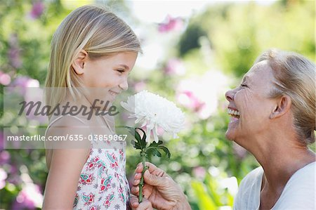 Grandmother giving flower to granddaughter in garden Stock Photo - Premium Royalty-Free, Image code: 635-03859867