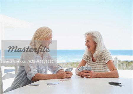 Senior women playing cards on beach patio Stock Photo - Premium Royalty-Free, Image code: 635-03859882