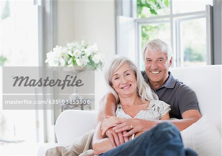 Senior couple hugging on sofa in living room Stock Photo - Premium Royalty-Free, Image code: 635-03859906