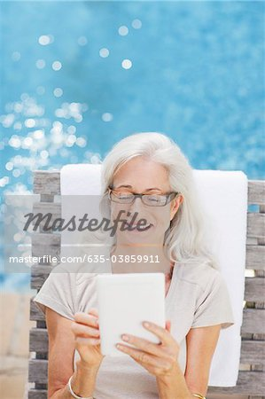 Senior woman using digital tablet poolside Stock Photo - Premium Royalty-Free, Image code: 635-03859911