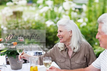Senior couple drinking wine at table in garden Stock Photo - Premium Royalty-Free, Image code: 635-03859936