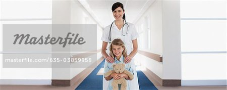 Nurse and child patient with teddy bear in hospital corridor Stock Photo - Premium Royalty-Free, Image code: 635-03859958