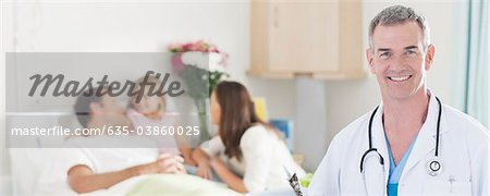 Portrait of pediatrician in hospital with family in background Stock Photo - Premium Royalty-Free, Image code: 635-03860025