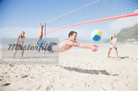Friends playing volleyball on beach Stock Photo - Premium Royalty-Free, Image code: 635-03860161