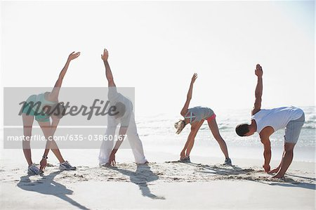 Friends stretching on beach Stock Photo - Premium Royalty-Free, Image code: 635-03860167