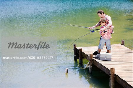Father and son fishing off dock Stock Photo - Premium Royalty-Free, Image code: 635-03860177