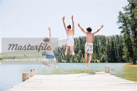 Kids jumping off dock into lake Stock Photo - Premium Royalty-Free, Image code: 635-03860205