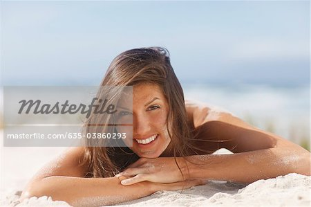 Woman laying on beach Stock Photo - Premium Royalty-Free, Image code: 635-03860293
